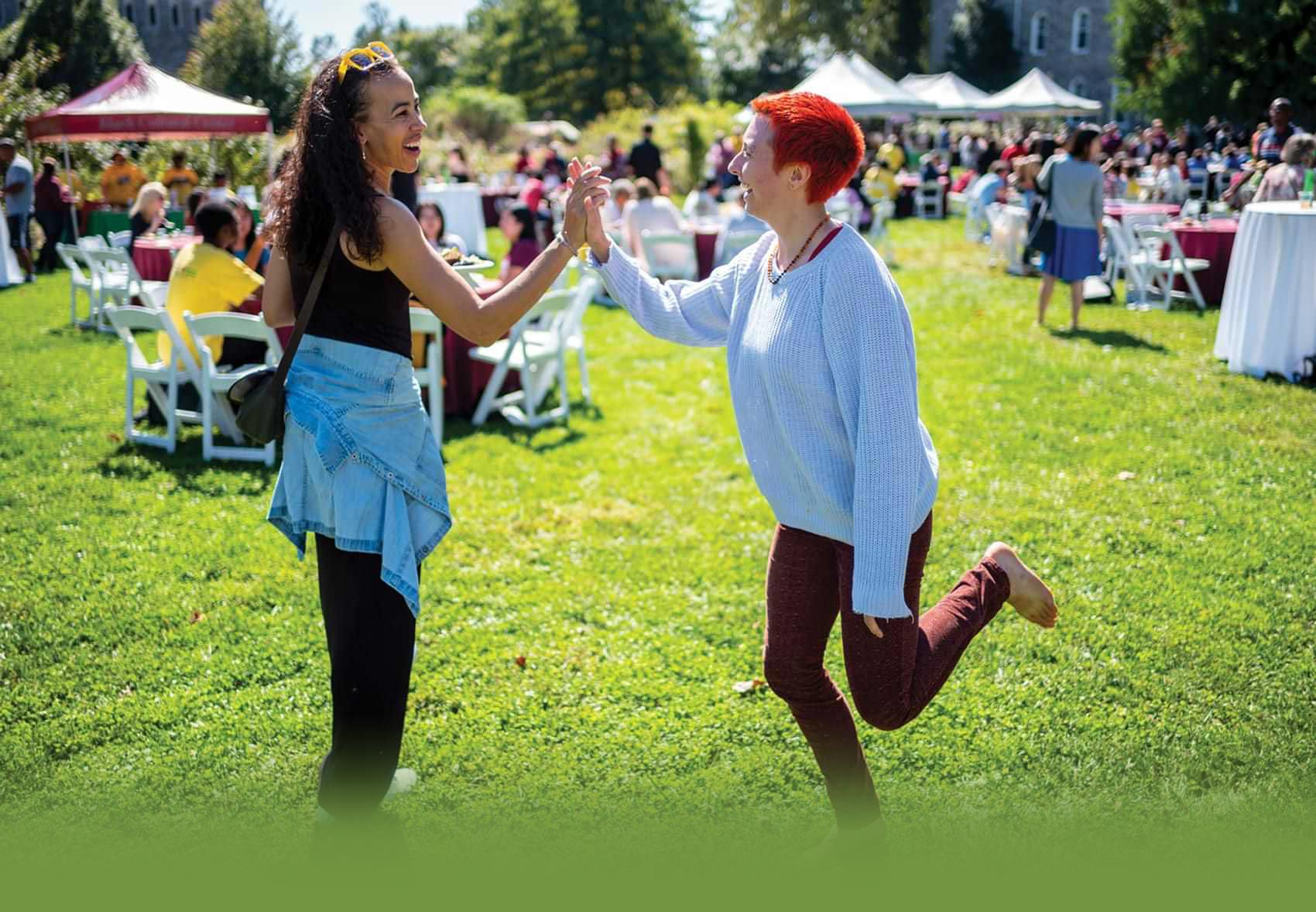 students say hi with a high-five at an outdoor event